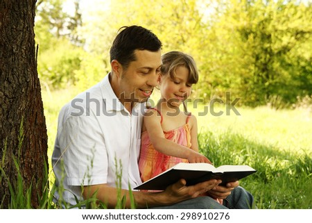 a young father with his little daughter reading the Bible - stock photo