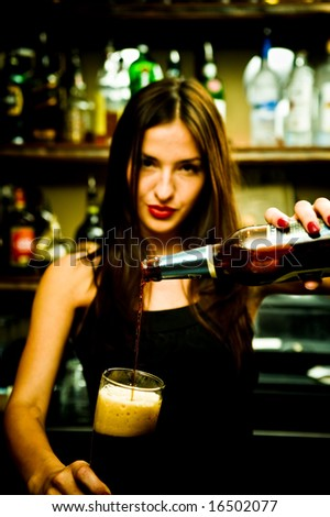 A young female bartender, photographed at work. - stock photo