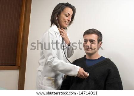 A young, female doctor, checks the pulse of a patient through his heart. - vertically framed - stock photo