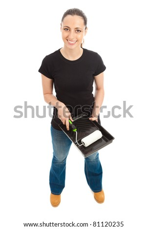 A young female dressed in a black t shirt and blue jeans holding a paint roller and tray