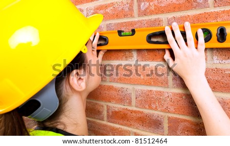 A young female in a hard hat checking if brick wall is level