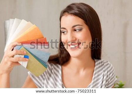 A young female looking at a group of color swatches - stock photo