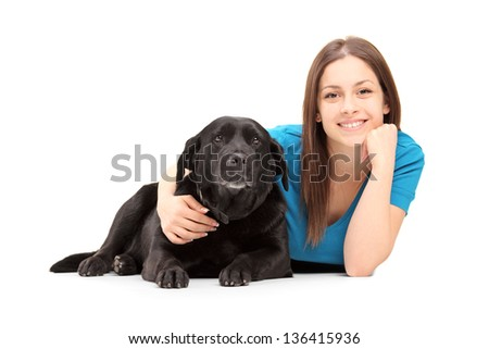 A young female lying and posing with a black dog isolated on white background - stock photo