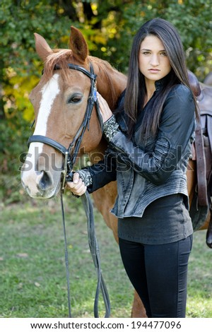 A young female model posing with a horse on a sunny day. - stock photo