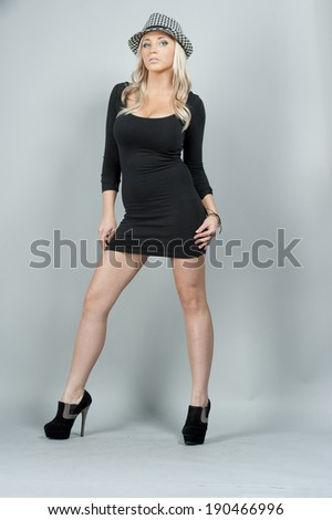 A young female model wearing a black dress and shoes in a studio setting.