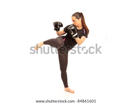 A young female performing a martial arts kick on an isolated white background - stock photo
