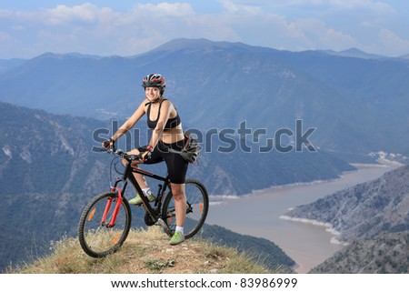 A young female posing with a mountain bike with lake in the background