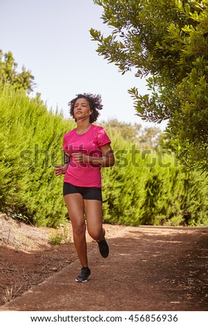 A young female runner out for a jog on a gravel path surrounded by bushes, wearing casual running clothes in the late morning shadows