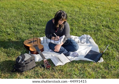 A young female singer or song writer with her guitar and computer outdoors in the grass. - stock photo