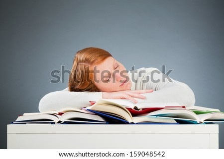 A young female student sleeping on her desk over a pile of open books instead of studying. - stock photo