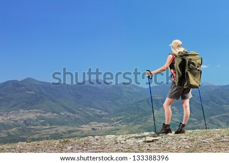 A young female with backpack and hiking poles in the mountain - stock photo