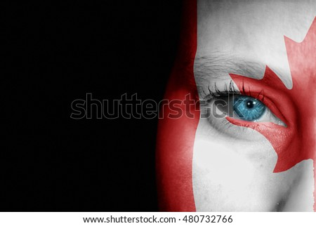 A young female with the flag of Canada painted on her face on her way to a sporting event to show her support.