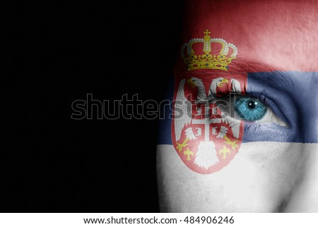 A young female with the flag of Serbia painted on her face on her way to a sporting event to show her support.