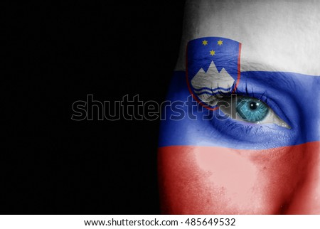 A young female with the flag of Slovenia painted on her face on her way to a sporting event to show her support.