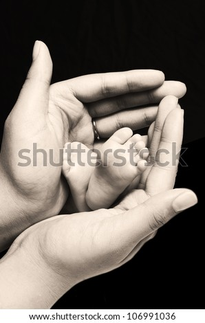 A young first time mother is holding the feet of her first new born baby girl and gently enclosing her soft and warm fingers and palms around the tiny feet and toes - stock photo