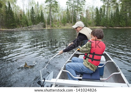 A young fisherman in a canoe catches a walleye - stock photo