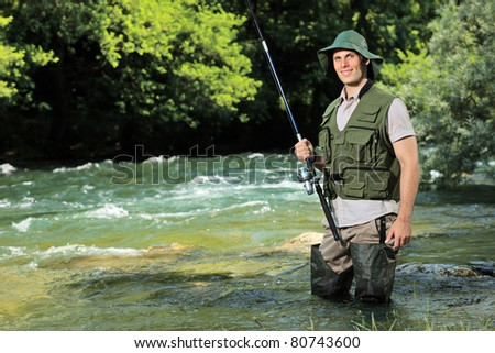 A young fisherman posing with fishing pole in his hand on a river Treska, Macedonia - stock photo