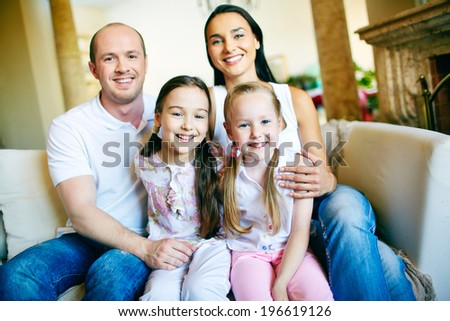 A young friendly family of four looking at camera at home - stock photo