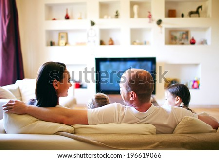 A young friendly family of four spending weekend at home - stock photo