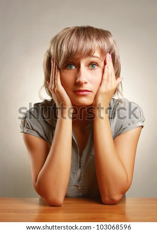 A young frightened woman sitting at the desk, isolated on grey - stock photo
