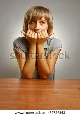 A young frightened woman sitting at the desk, isolated on grey