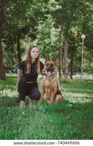A young girl, a woman in black, wearing glasses, sits with a German shepherd in a city park, a forest. Summer