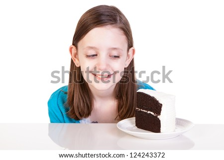 A young girl about to eat a piece of white frosting chocolate cake