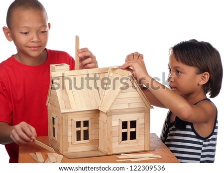 A young girl and boy enjoy building a wooden toy house together. - stock photo