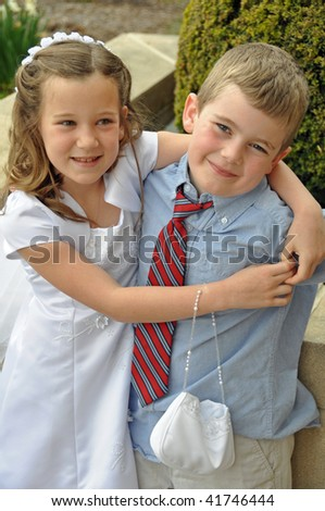 a young girl and boy hug on first communion day - stock photo