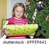 A young girl at her Christmas tree holding a wrapped gift. - stock photo