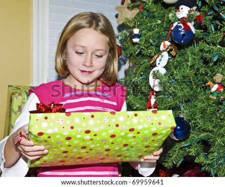A young girl at her Christmas tree holding a wrapped gift.