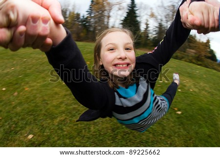 A young girl being spun in circles by her Dad at a park outside. - stock photo