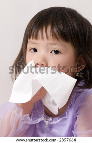 A young girl blows her nose, it's flu season. - stock photo