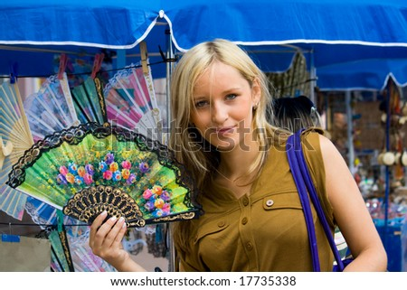 a young girl chooses a fan on the market - stock photo