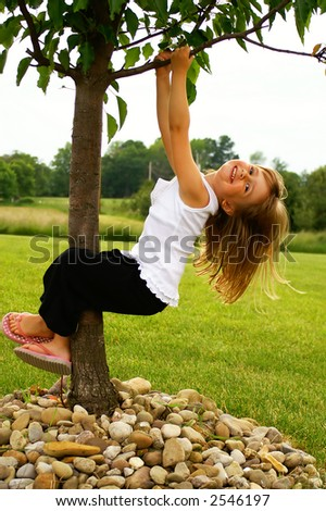 A young girl climbing a tree - stock photo