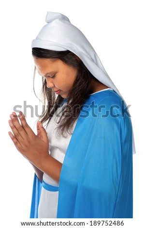 A young girl closes her eyes and assumes a praying position. - stock photo