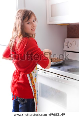 A young girl cooking in a white kitchen - stock photo