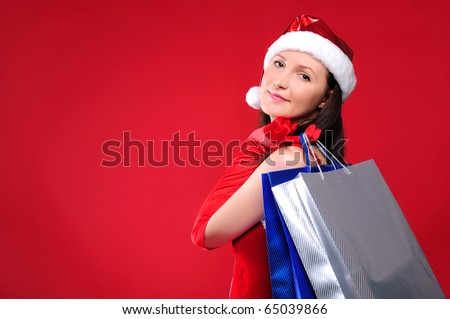 a young girl dressed as Santa Claus on a red background is engaged in shopping. A girl holding shopping bags. Happy New Year and Merry Christmas! - stock photo