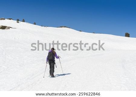 A young girl during a trip snowshoeing, in a snowy landscape.