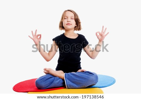 A young girl engaged in yoga on a multi-colored yoga mat. - stock photo