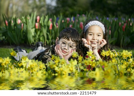 A young girl enjoying the flower park with her younger brother. - stock photo