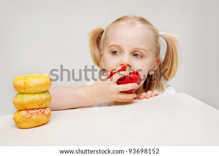 A young girl enjoys a healthy apple while she looks towards unhealthy donuts.