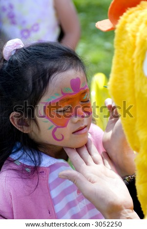 A young girl gets her face painted with bright colors. - stock photo