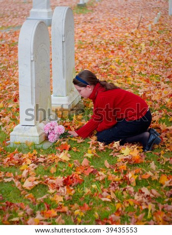 A young girl grieves at a grave - stock photo