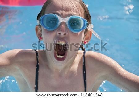 A young girl having fun in a swimming pool wearing swimming goggles. - stock photo