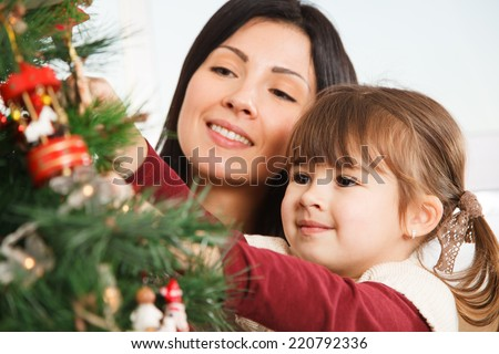A young girl helps her mother to decorate the family Christmas tree - stock photo