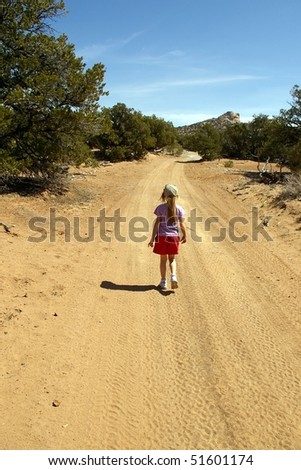 A young girl hikes down a dusty desert road.