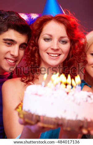 A young girl holding a birthday cake with candles and smiling among her two friends