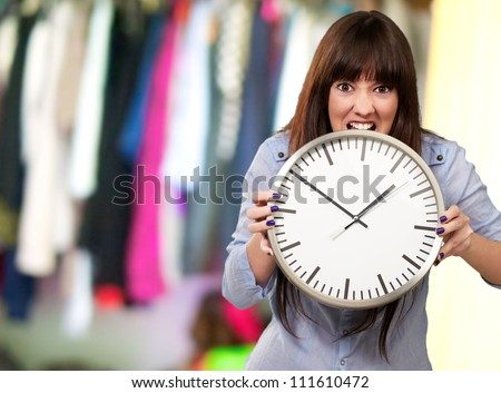 A Young Girl Holding A Clock And Angry, Indoor - stock photo