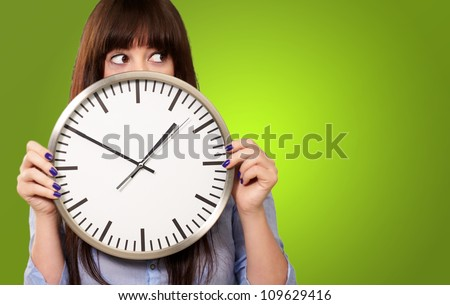A Young Girl Holding A Clock On Green Background - stock photo